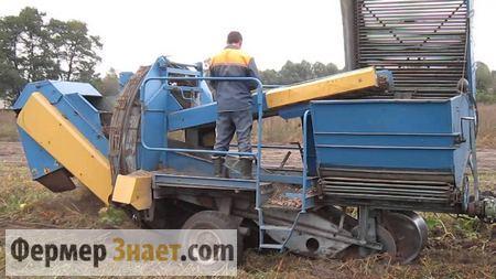 Комбайн собирает урожай картошки