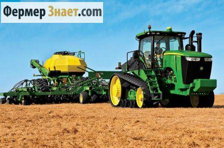 Гусеничный трактор пашет в поле
